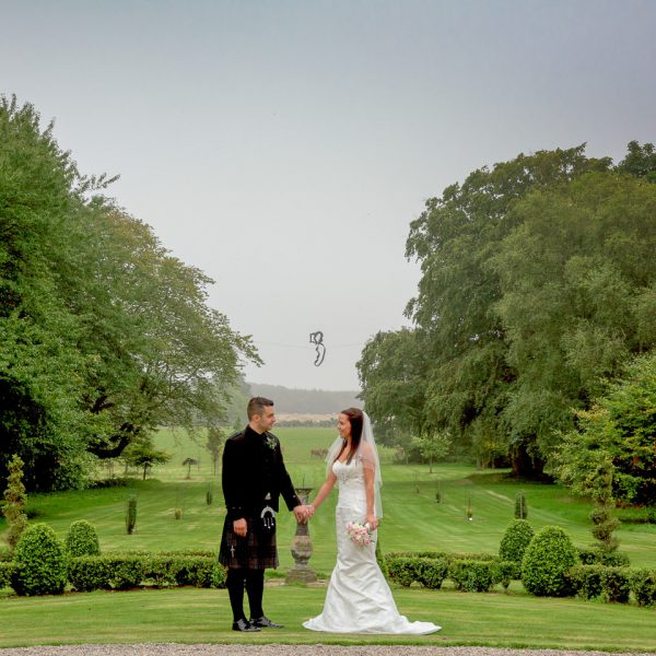 Aberdeen Wedding Photographer - Bride and groom posing on front lawn of Crimonmogate Estate, Aberdeenshire